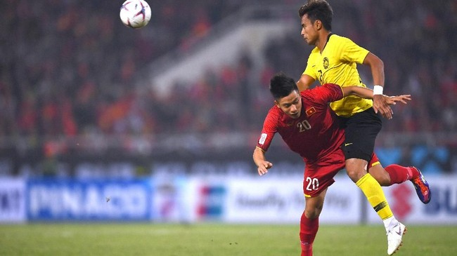 Bek Malaysia Aidil Zafuan (kanan) berduel dengan winger Vietnam Phan Van Duc. Dalam laga tersebut timnas Malaysia lebih mendominasi permainan dengan penguasan bola mencapai 58 persen. (Photo by Manan VATSYAYANA / AFP)