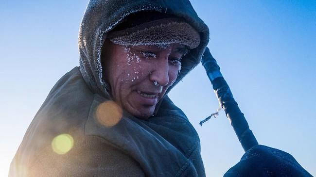 Salah seorang warga Yakutsk, Innokenty Tobonov, misalnya, yang bersusah payah memotong balok es dari danau bersuhu minus 41 derajat Celcius untuk menjadikannya air minum. (Photo by Mladen ANTONOV/AFP)