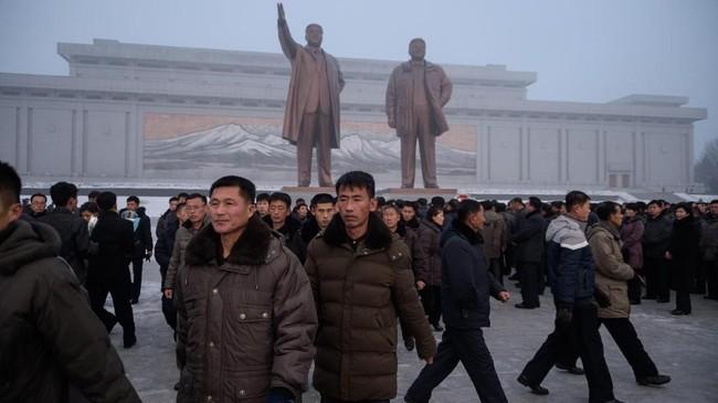 Warga Korea Utara berkumpul di depan patung Kim Jong-il untuk memperingati tujuh tahun kematian sang pemimpin serta menyatakan kesetiaan pada putranya yang kini memegang takhta, Kim Jong-un. (AFP Photo/Kim Won Jin)