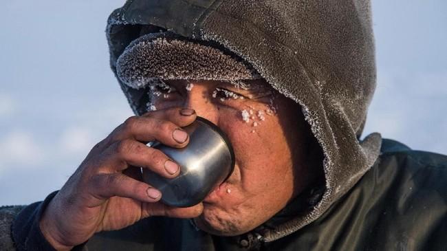 Beberapa warga terbiasa meminumnya mentah. Namun, beberapa warga yang lain memilih untuk memanaskannya terlebih dahulu. Menurut mereka, air dari balok es yang meleleh begitu saja tak punya banyak kandungan kalsium dan magnesium yang diperlukan tubuh.(Photo by Mladen ANTONOV/AFP)