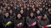 Di tengah hujan salju pada Minggu (16/12), para warga Korut berduyun-duyun ke pusat kota untuk memberikan hormat di depan patung yang terletak di Mansu Hill, Pyongyang, tersebut. (AFP Photo/Kim Won Jin)