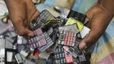 Di rumahnya, Koffi menghancurkan ponsel-ponsel itu untuk memisahkan layar dan keyboards. Keduanya adalah elemen penting untuk proyek seni ini. (REUTERS/Luc Gnago)