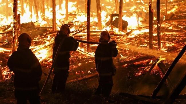Api mulai menyala pada Senin malam dan terus merembet karena pemadam kebakaran membutuhkan waktu berjam-jam untuk mematikan kobaran tersebut. (AFP Photo/Michael Dantas)
