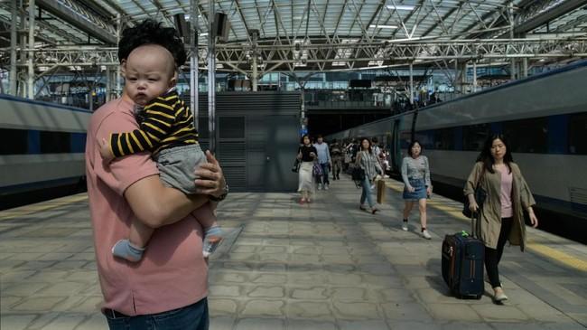 Sederet faktor melatarbelakangi hal tersebut. Mulai dari biaya membesarkan anak, jam kerja yang panjang, dan tempat penitipan anak yang terbatas. Faktor-faktor ini pada akhirnya bakal menjadi kemunduran karier bagi ibu bekerja. (Photo by Ed JONES/AFP)