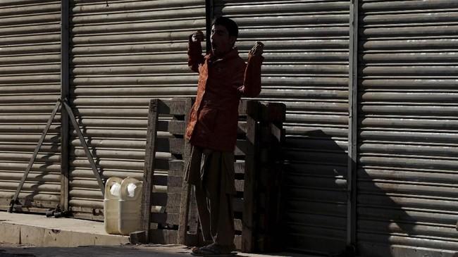 Seorang bocah laki-laki menguap di bawah sinar matahari di depan toko-toko yang tutup pada pagi hari di Karachi, Pakistan. Pertumbuhan ekonomi Pakistan diperkirakan mencapai titik terendah sembilan tahun, merosot ke hampir 2,9 persen. (REUTERS/Akhtar Soomro)