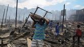 Para penduduk pun langsung berhamburan keluar rumah sambil membawa harta benda yang bisa mereka gotong. (AFP Photo/Michael Dantas)