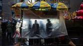 Para pedagang makanan jalanan berteduh ketika hujan datang di kota Manhattan, New York, Amerika Serikat. (REUTERS/Amr Alfiky)