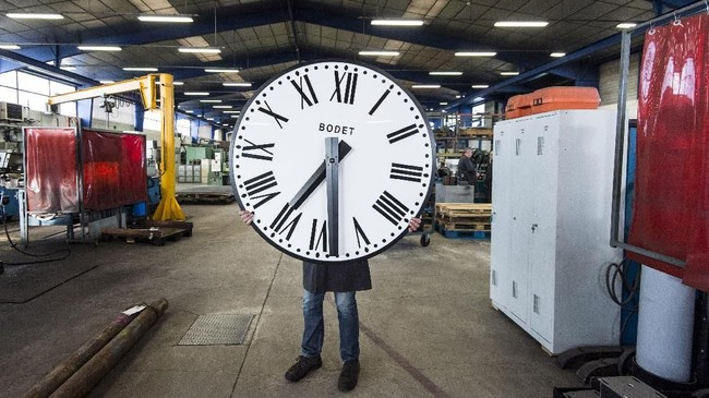 Seorang pegawai perusahaan Bodet membawa jam dari sebuah menara di bagian barat Perancis. Perusahaan itu telah memproduksi jam-jam besar untuk gereja, stasiun, atau gedung olahraga sejak 1868. (Photo by Sebastien SALOM-GOMIS / AFP)