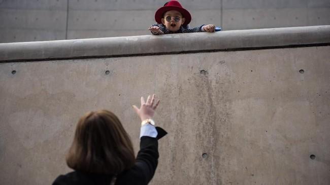 Seorang bocah mengarahkan pandangan pada seorang wanita di Plaza Dongdaemun di Seoul. Di Korea Selatan, tingkat kesuburan wanita jatuh ke angka 0,95 pada kuarter ketiga 2018, menandai pertama kalinya angka ini jatuh ke bawah 1. (Photo by Ed JONES / AFP)
