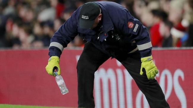Petugas lapangan memungut botol yang dilempar ke arah Dele Alli. (Reuters/Andrew Couldridge)