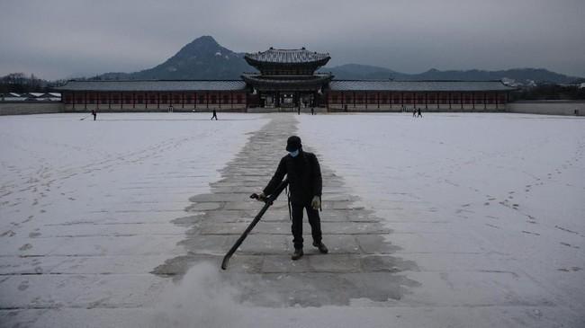 Pekerja terlihat membersihkan jalanan di Istana Gyeongbokgung dari tumpukan salju.