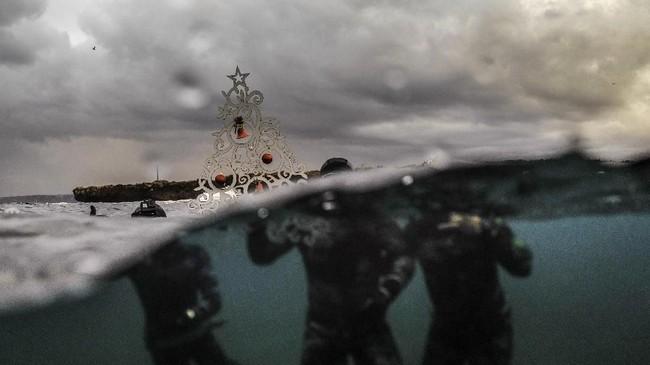 Para penyelam bebas berpose dengan pohon natal berornamen sebelum kembali menyelam dan menempatkan pohon natal itu di dasar laut perairan utara kota Tripoli, Libanon. (Photo by IBRAHIM CHALHOUB / AFP)