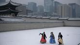Turis berpakaian tradisional Korea Selatan, hanbok, melintas di komplek Istana Gyeongbokgung yang diselimuti salju.
