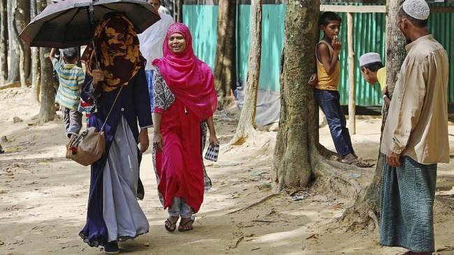 Namun, ia terus mempertahankan posisi kartu identitas yang menggantung di lehernya. (Reuters/Mohammad Ponir Hossain)