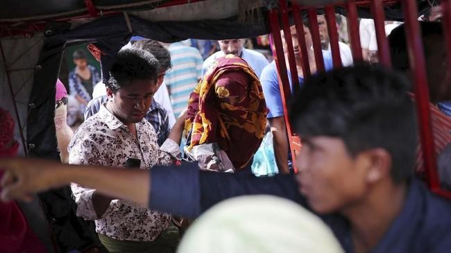 Sementara yang lain bersenda gurau, Akter hanya terdiam membawa koper, menunduk di tengah keriuhan. (Reuters/Mohammad Ponir Hossain)