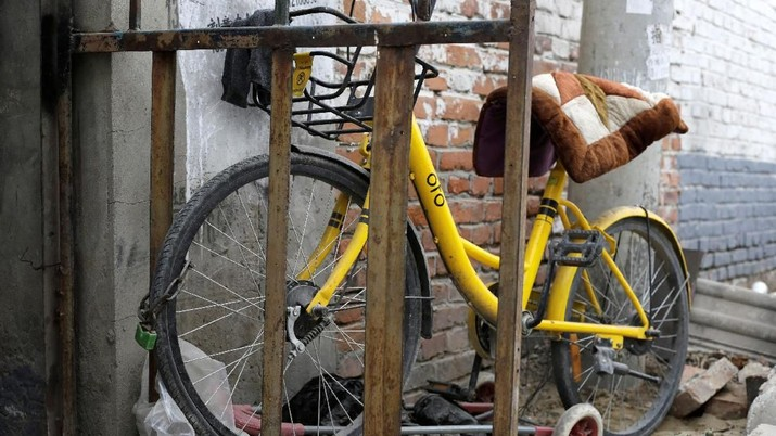 A damaged Ofo bike-sharing bicycle lies in debris in a village on the outskirts of Beijing, China December 22, 2018. REUTERS/Jason Lee