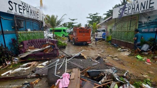 Usai tsunami menerjang, sirine peringatan tsunami sempat berbunyi yang menimbulkan kepanikan warga. Warga berbondong-bondong mengungsi ke dataran tinggi. (Photo by Ronald / AFP)
