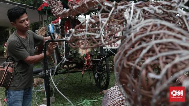 Pekerja mendekorasi ornamen Natal di Gereja Katedral, Jakarta, Minggu (23/12). Gereja Katedral mempersiapkan dekorasi ruangan dan perbaikan lampu hias di delman rusa yang terbuat dari rotan menjelang Natal. (CNN Indonesia/Andry Novelino)