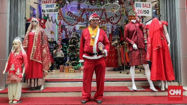 Seorang karyawan toko mengenakan kostum santa claus untuk menarik perhatian pengunjung dengan menawarkan produk busana yang diskon menyambut Natal di kawasan Pasar Baru, Jakarta, Jumat, 14 Desember 2018. (CNNIndonesia/Safir Makki)