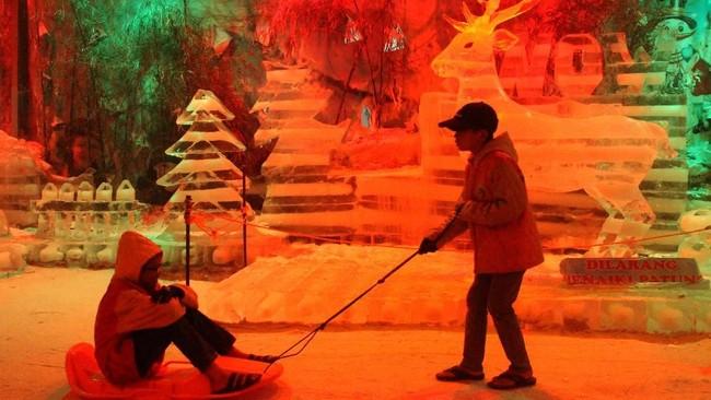 Pengunjung melintas di depan latar patung es bernuansa Natal di Wahana Ormanen dan Patung Es Snow World, Bekasi, Jawa Barat, Kamis (20/12). Wahana ornamen patung es tersebut menampilkan sekitar 40 ormanen dan patung es, sebagai wisata liburan Hari Raya Natal dan Tahun Baru 2019. (Antara/Risky Andrianto)