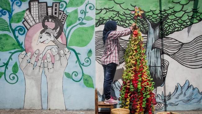 Warga menyelesaikan pembuatan instalasi pohon Natal berbahan limbah botol plastik di Purwosari, Solo, Jawa Tengah, Rabu (19/12). Mereka menghias kampung dengan membuat instalasi pohon Natal memanfaatkan limbah botol plastik untuk menyambut Natal 2018 sekaligus mengampanyekan gerakan peduli lingkungan. (Antara/Mohammad Ayudha)