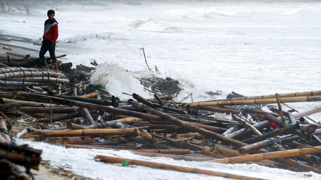 Seorang warga yang terdampak tsunami Selat Sunda memerhatikan puing-puing terserak di Pantai Carita, Pandeglang, Banten, 24Desember 2018. (REUTERS/Jorge Silva)