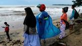 Warga sekitar memerhatikan laut di pesisir Pantai Carita, Senin, 24 Desember 2018. Pantai Carita menjadi salah satu pesisir Banten yang terhantam tsunami Selat Sunda akibat aktivitas vulkanis Gunung Anak Krakatau. (REUTERS/Jorge Silva)