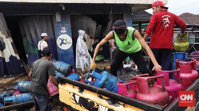 Warga merapikan tabung-tabung gas di antara reruntuhan sisa tsunami di Desa Sumberjaya, Kecamatan Sumur, Pandeglang, Banten, Senin (24/12). CNN Indonesia/Hesti Rika