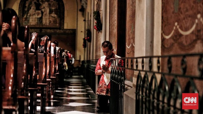 """Umat Katolik beribadah malam Natal di Gereja Katedral, Jakarta. Senin 24 Desember 2018. Misa malam Natal 2018 mengusung tema """"Yesus Kristus Hikmat Bagi Kita"""" dengan Misa yang dipimpin oleh Pastur Romo Albertus Hani Rudi Hartoko dari Paroki Katedral Jakarta. (CNN Indonesia/Andry Novelino)"""