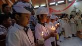 Sejumlah anak berbusana adat Bali membawa lilin saat mengikuti prosesi misa malam Natal di Gereja Katolik Hati Kudus Yesus Palasari, Jembrana, Bali, Senin (24/12/2018). Misa malam Natal dengan berpakaian adat Bali merupakan tradisi umat Katolik di Desa Palasari sebagai simbol akulturasi. (ANTARA FOTO/Nyoman Hendra Wibowo/nym/kye)
