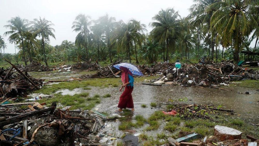 Warga berjalan di tengah hujan melewati puing-puing rumahnya yang rusak setelah tsunami di Sumur, Banten, Rabu (26/12/2018). REUTERS/Jorge Silva