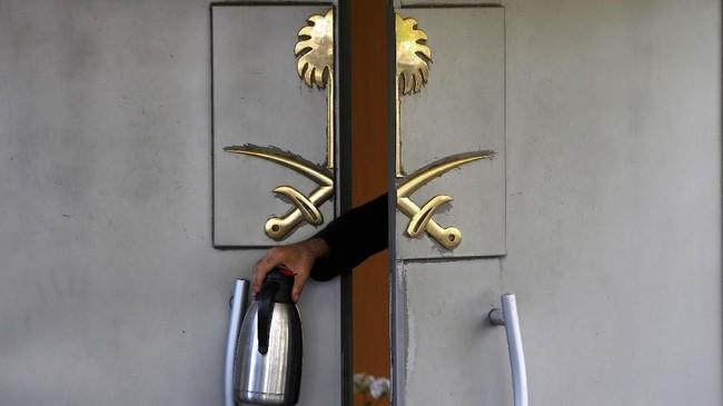 Seorang staf memegang termos di pintu masuk Konsulat Arab Saudi di Istanbul, Turki, tempat jurnalis Jamal Khashoggi dibunuh pada 2 Oktober 2018. (REUTERS/Osman Orsal)