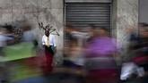 Satu pria hanya bisa bersandar di tembok ketika orang lain berlarian di tengah situasi padam listrik di Caracas. (Photo by FEDERICO PARRA / AFP)