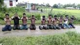 Sepuluh pria Muslim Rohingya berlutut dengan tangan terlipat di belakang kepala sebelum dibantai di Desa Inn Din, Myanmar. (Handout via REUTERS)