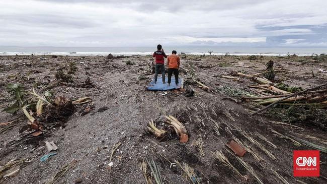 Dua pekerja melaksanakan salat zuhur di pinggir pantai yang rusak akibat terjangan tsunami di Pantai Tanjung Jaya, Kecamatan Panimbang, Banten, Rabu, 26 Desember 2018. (CNNIndonesia/Safir Makki)