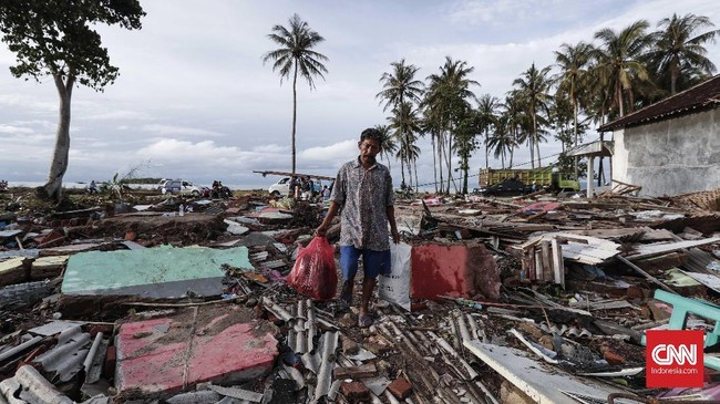Seorang warga berada di tengah reruntuhan permukiman Desa Sumber Jaya yang diterjang Tsunami Selat Sunda akibat aktivitas vulkanis Gunung Anak Krakatau, Desa ini merupakan salah satu lokasi paling parahdan sempat terisolasi setelahnya. (CNNIndonesia/Safir Makki)