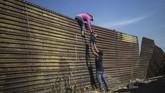 Sekelompok imigran Timur Amerika memanjat tembok perbatasan di dekat El Chaparral yang membatasi wilayahMeksiko dan Amerika Serikat.