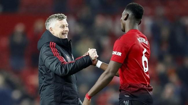 Gelandang Manchester United Paul Pogba bersalaman dengan Ole Gunnar Solskjaer usai kemenangan 3-1 atas Huddersfield. Sebelumnya, Man United sukses menang 5-1 atas Cardiff City. (Reuters/Jason Cairnduff)
