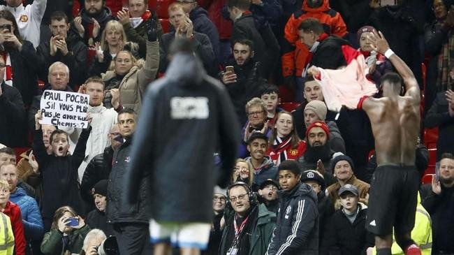 Paul Pogba membuka baju dan memberi kostum pertandingan melawan Huddersfield kepada seorang suporter Manchester United usai laga. (Reuters/Jason Cairnduff)