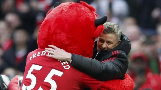 Ole Gunnar Solskjaer berpelukan dengan maskot Manchester United jelang pertandingan melawan Huddersfield Town di Stadion Old Trafford, Rabu (26/12) malam waktu setempat. (REUTERS/David Klein)