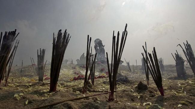 Di pantai Marina di Chennai, India, kayu-kayu dupa terbakar sementara seorang gadis kecil berdoa untuk korban-korban tsunami 2004. (REUTERS/P. Ravikumar)