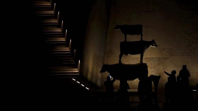 Di Valletta, Malta, orang-orang melihat instalasi seni yang menggambarkan tiga ekor sapi, simbol peribahasa Malta yang secara harfiah berarti