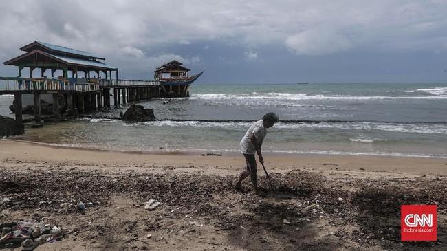 Emi Suryo, pemilik resort membersihkan sisa dahan dan ranting pohon yang terbawa gelombang tsunami di kawasan Anyer, Serang, Banten, 27 Desember 2018. Emi tetap optimis usaha resortnya bisa bangkit. (CNNIndonesia/Safir Makki)