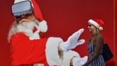 Seorang perempuan berjalan melewati poster raksasa Santa Klaus di pantai Jumeirah di Dubai. (GIUSEPPE CACACE / AFP)