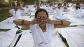 Seorang perempuan India berpartisipasi pada suatu sesi Yoga di Mahila Yoga Shakti Divas di Nikol, Ahmedabad. Lebih dari 700 perempuan berpartisipasi pada ajang yang digelar oleh Bhartiya Yoga Sansthan tersebut. (SAM PANTHAKY / AFP)
