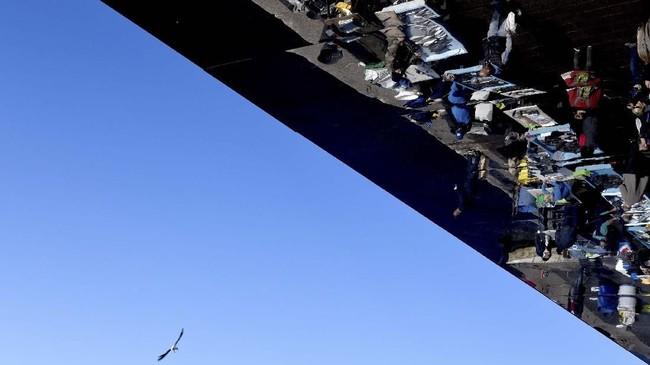 Seekor burung camar terbang dekat seorang penjual ikan yang bayangannya tercermin di atap L'Ombriere yang dirancang oleh arsitek Inggris, Norman Foster, dan didirikan di atas air di pelabuhan lama di kota Marseille, Perancis. (GERARD JULIEN / AFP)
