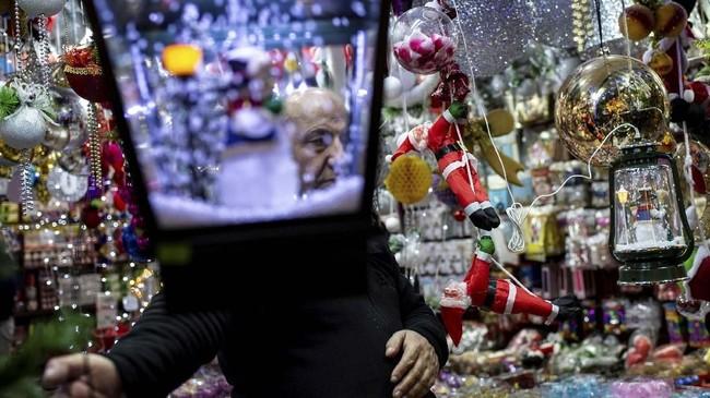 Seorang pria berdiri dekat ornamen-ornamen natal di Bazar Eminonu di Istanbul, Turki. (Yasin AKGUL / AFP)