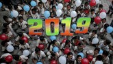 Pelajar memegang balon menyambut pesta pergantian tahun di sekolah mereka di Ahmedabad, India, Senin (31/12). (Reuters/Amit Dave)