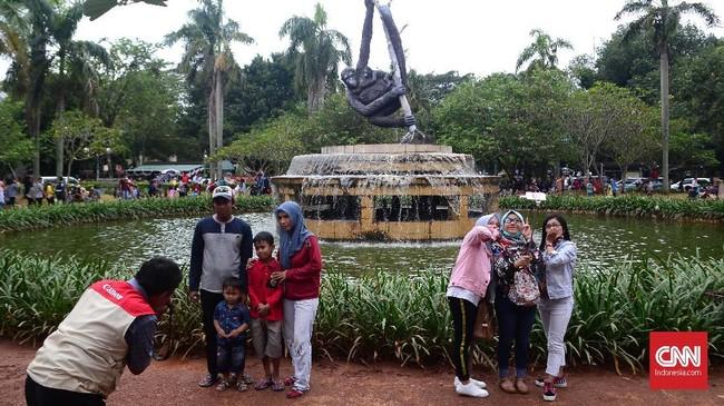 Pengunjung Ragunan meminta petugas foto untuk mengabadikan momen keluarga mereka di kebun binatang tersebut. Ada pula yang memilih berswafoto bersama dengan bantuan tongkat swafoto.(CNN Indonesia/ Harvey Darian)