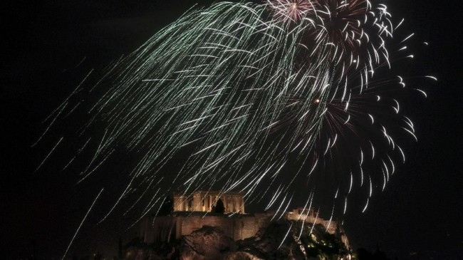 Di atas Acropolis, Athena, Yunani, semarak kembang api juga jadi penanda tahun berganti. (Reuters/Yannis Behrakis)